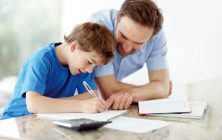 Father helping son with his schoolwork